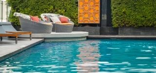 commercial swimming pool with nice chairs around it