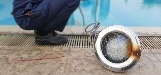 pool repair guy replacing burnt out pool light