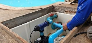 pool repair man fixing pool pump